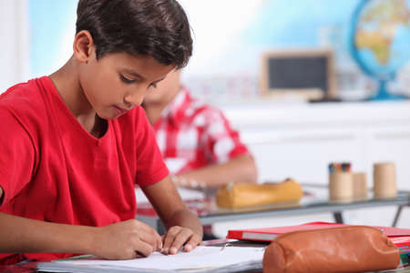 little boy focusing on his work in classroom photo