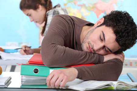 Young man sleeping during a university lecture photo