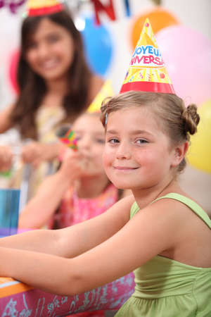 a little girl and her friends at a birthday party photo