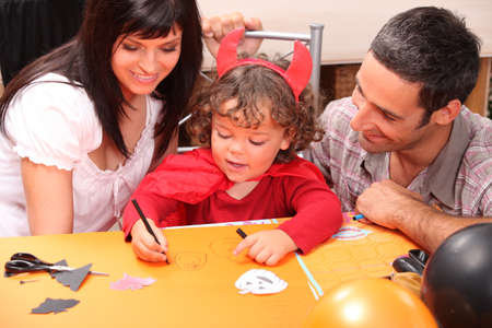 Little boy in Halloween costume with his parents photo