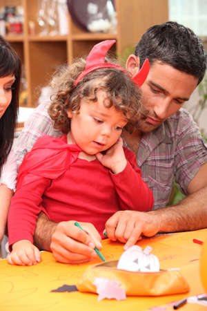 Parents helping child with Halloween decorations photo