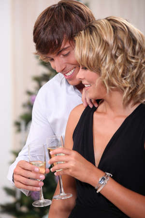 20 23 years: Couple drinking champagne in front of a Christmas tree