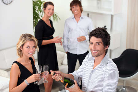 two well dressed couples drinking sparkling wine in a living room photo