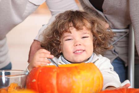 A plump kid carving a pumpkin. photo