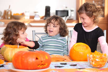Three sisters carving pumpkins. photo