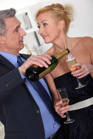 personas celebrando: Pareja joven bebiendo champ�n