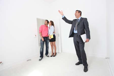 courtier: Couple �tant repr�sent� autour de la propri�t� par des biens-agent Banque d'images