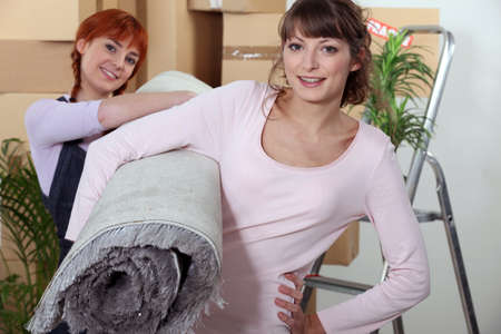 roommates: Young women carrying a rolled-up rug on moving day