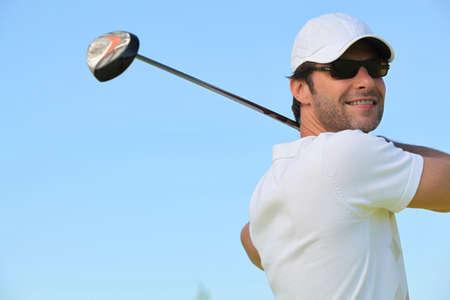 golf cap: man playing golf
