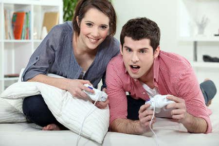jugando videojuegos: Pareja joven jugando un juego de v�deo a la vez Foto de archivo