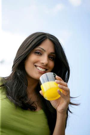 Woman drinking glass of orange juice outdoors photo