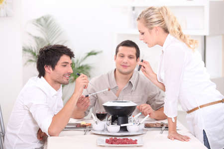 Three people enjoying fondue photo