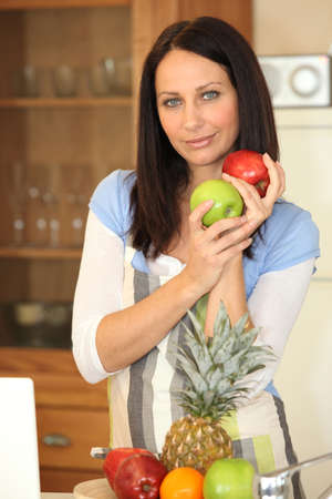 Woman with fruit in a kitchen Stock Photo - 11612290