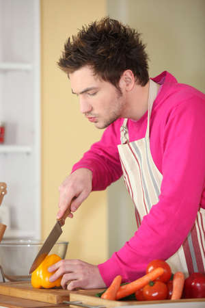 young man in kitchen cooking photo