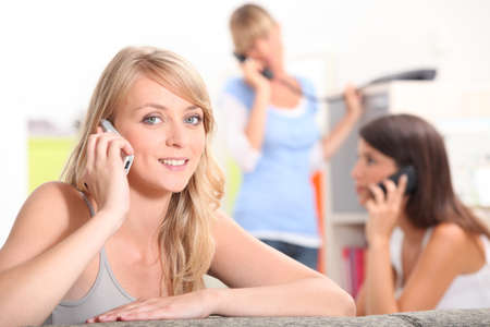 roommates: three girlfriends in their apartment talking on their cells