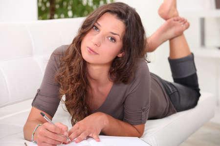 journal intime: Jeune femme couch�e sur un canap� une �criture dans un journal Banque d'images