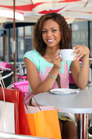 metis: 20 years old metis woman is drinking coffee on a terrace, she did shopping before Stock Photo