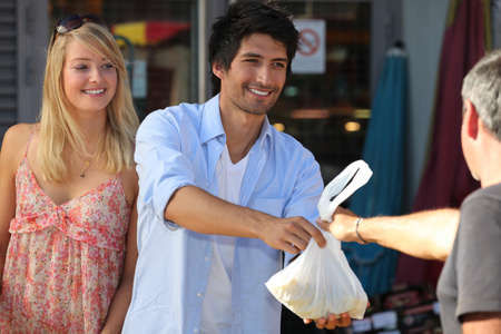 retailer: Young couple making purchases at the market