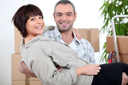 Man carrying his wife over the threshold photo