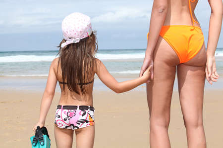 toweling: Mother and daughter holding hands on a sandy beach Stock Photo