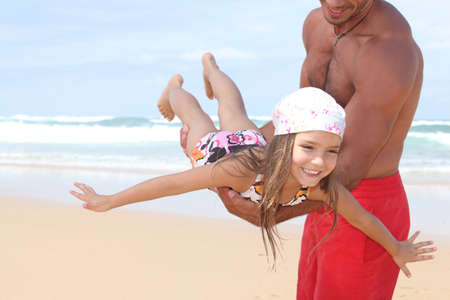 Man flying his daughter around a beach photo