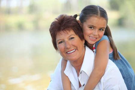 háton: Fiatal lány lovaglás piggy-back on nagyanyját Stock fotó