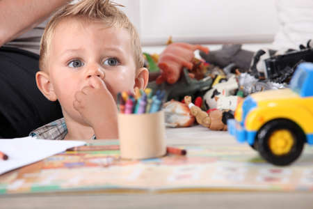 Little boy drawing with crayons photo