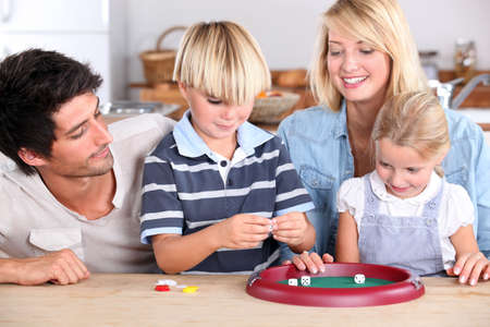 Family playing game at kitchen table photo