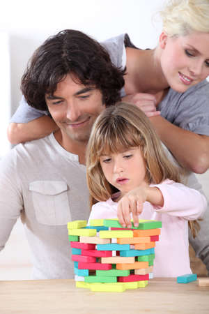 adroitness: parents looking her daughter playing with blocks Stock Photo