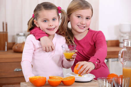 two little girls drinking orange juice photo