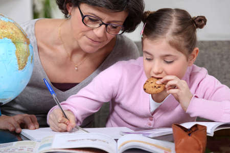 Woman helping her granddaughter with her homework photo