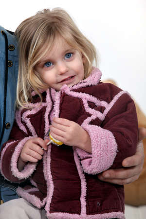 Young girl wearing a coat and holding a lolly Stock Photo - 11613252