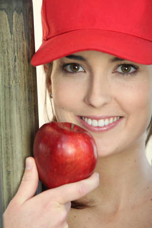 advised: woman wearing a cap and eating an apple Stock Photo
