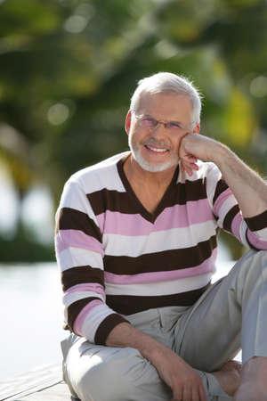 hombre sentado: Anciano se sent� en el jard�n Foto de archivo