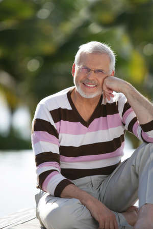 Elderly man sat in garden photo