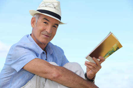 65 70 years: Carefree man reading a book outside Stock Photo