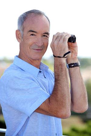 birdwatcher: Older man with a pair of binoculars Stock Photo