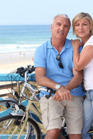 A middle aged couple biking by the seashore. photo