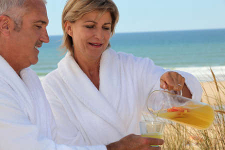 Mature couple drinking on beach photo