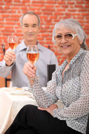 Elderly couple drinking wine in restaurant photo