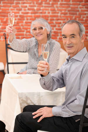 Elderly couple drinking champagne photo
