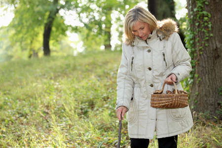 urban jungle: Middle-aged woman strolling through woods with basket