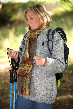50 55 years: Hiker using a compass in the woods Stock Photo