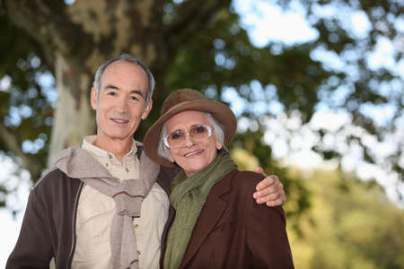 65 70 years: Elderly couple taking a walk together in the forest
