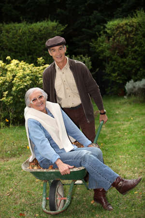 horseplay: Older couple messing around with a wheelbarrow