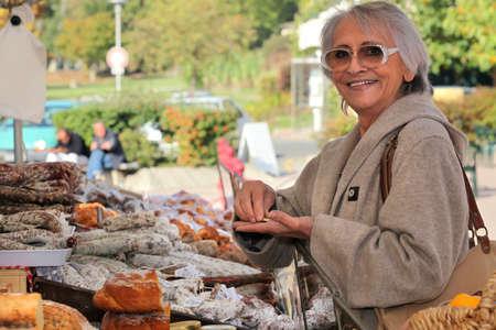openair: a senior woman  in an open-air market Stock Photo