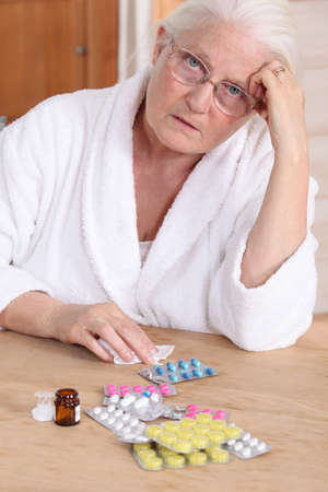 Senior woman in bathrobe about to take drugs photo