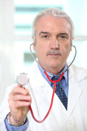 Doctor holding up the chestpiece of his stethoscope photo