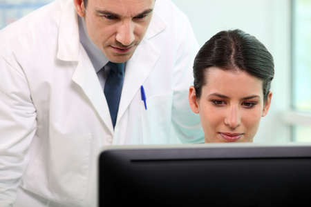 administrativo: Enfermera y m�dico mirando la pantalla del ordenador Foto de archivo