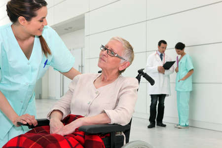 Nurse talking to an elderly woman in a wheelchair photo